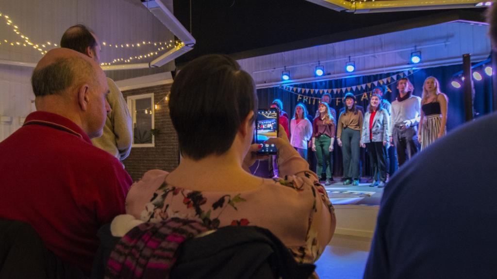 Publik tittar på människor som sjunger på en scen