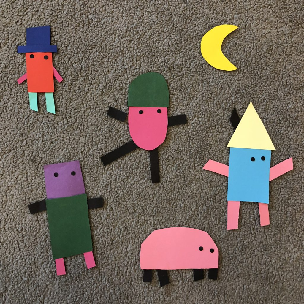 Sex pappersfigurer i olika färger som ligger på en grå matta