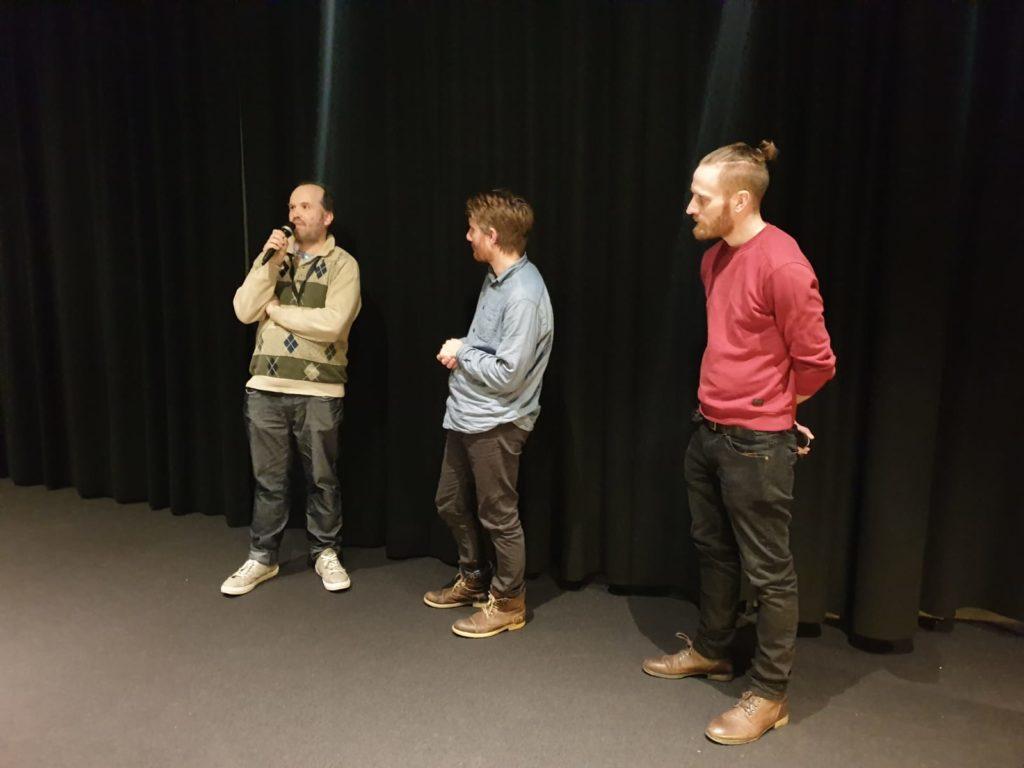 tre män står på en scen och pratar